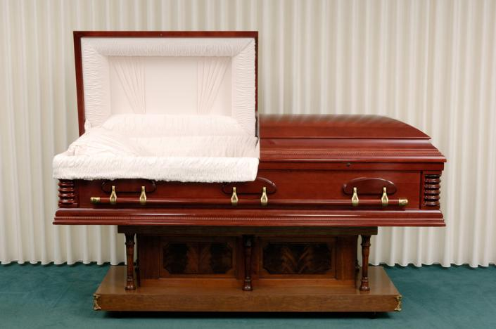 Deep reds, as found with cherry and mahogany, exhibit the natural elegance and style of a wooden casket.]